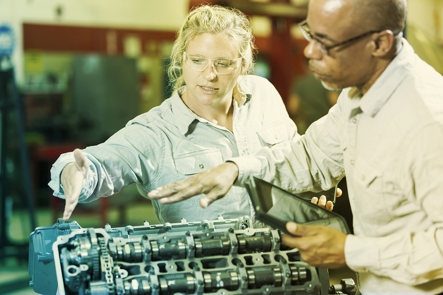 Two multi-ethnic mechanics working on a gasoline engine in a repair shop.  The African American man, in his 50s, is explaining to the trainee, a woman in her 20s, how to repair the engine.  He is holding a digital tablet.  The focus is on the woman